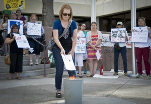 "mkb050815h/metro/Marla Brose/050815 Linnea Montoya, a kindergarten teacher at Montezuma Elementary, drops her teacher evaluation into a waste basket with other burning evaluations in front of Albuquerque Public Schools headquarters, Wednesday, May 20, 2015, in Albuquerque, N.M. A group of teachers filled the entrance to APS to participate in the teacher evaluation protest. ""It insulted my fellow teachers who mentored me and scored lower,"" Montoya said. (Marla Brose/Albuquerque Journal)"